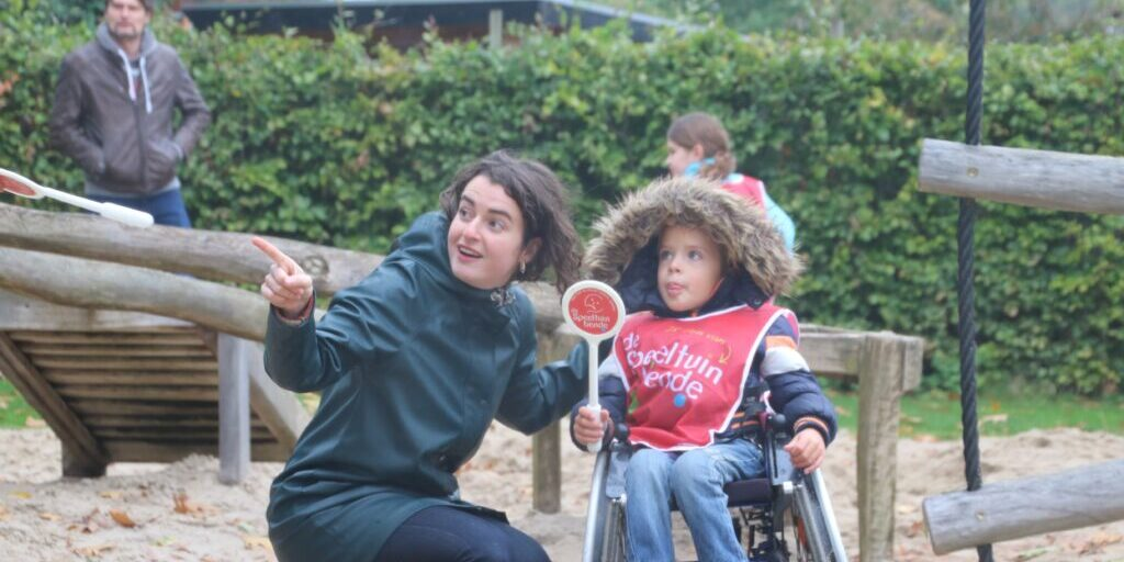 One off the researchers, L. van Engelen talking an playing with a child in a wheelchair.